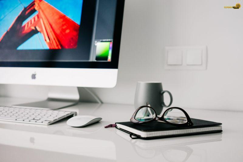 Foto de um computador em uma mesa brancos, com caderno, óculos e xícara ao lado. Imagem ilustrativa para texto franquias baratas para trabalhar em casa.