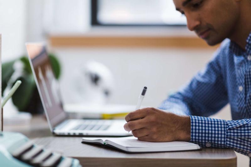 Homem de blusa azul escrevendo em um caderno. Ao lado vemos um computador, plantas e outros acessórios em uma mesa. Imagem ilustrativa para texto franquias baratas para trabalhar em casa.