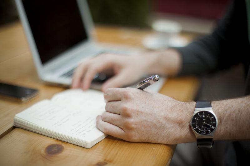 Mãos de uma pessoa fazendo anotações em um caderno com computador e celular ao lado. Imagem ilustrativa para texto franquias baratas para trabalhar em casa.