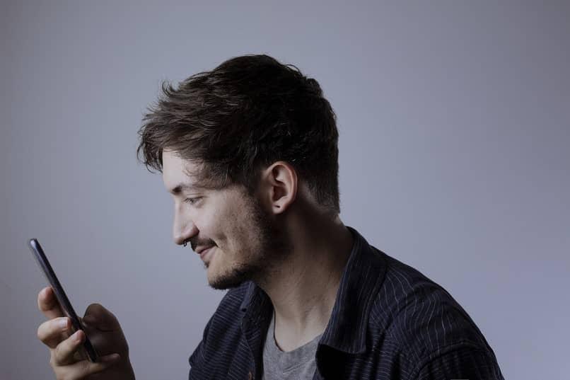 Rapaz de camisa preta usando um celular.