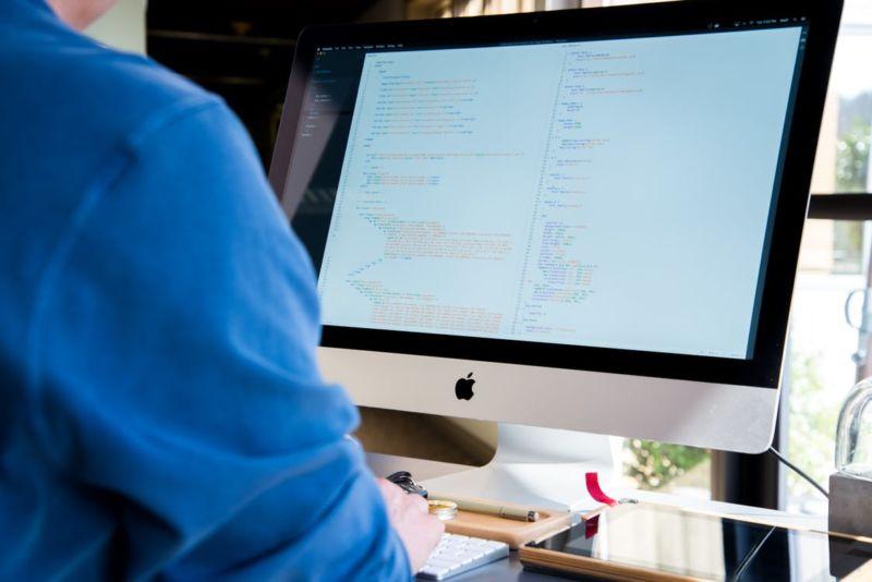 Homem de blusa azul usando um computador branco. Ao fundo vemos uma janela.