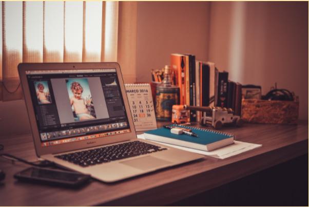 Imagem de uma mesa de home office com um computador e vários livros.