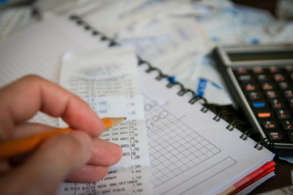 Imagem de uma mão fazendo anotações em uma conta e uma calculadora ao lado.