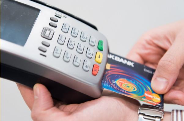 Imagem de uma máquina de cartão de crédito nas mãos de uma pessoa.