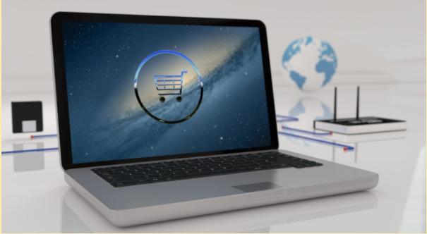 Imagem de um computador com a tela remetendo a compras online.