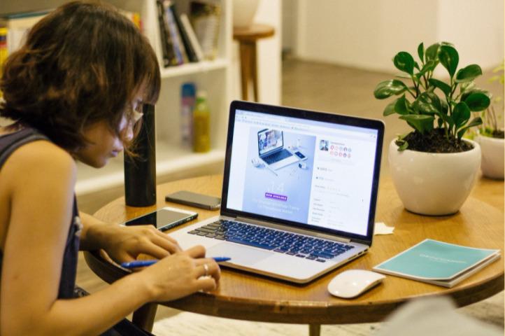 moça fazendo anotações, perto de um computador, em uma mesa com plantas, caderno e celular. Ao fundo vemos uma estante. Imagem ilustrativa para texto franquia home