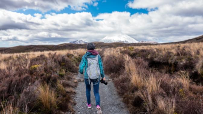 menina com mochila no meio de um campo, segurando uma máquina fotográfica.