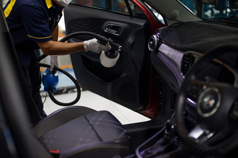 Pessoa usando um aparelho para fazer a limpeza interna de um veículo.