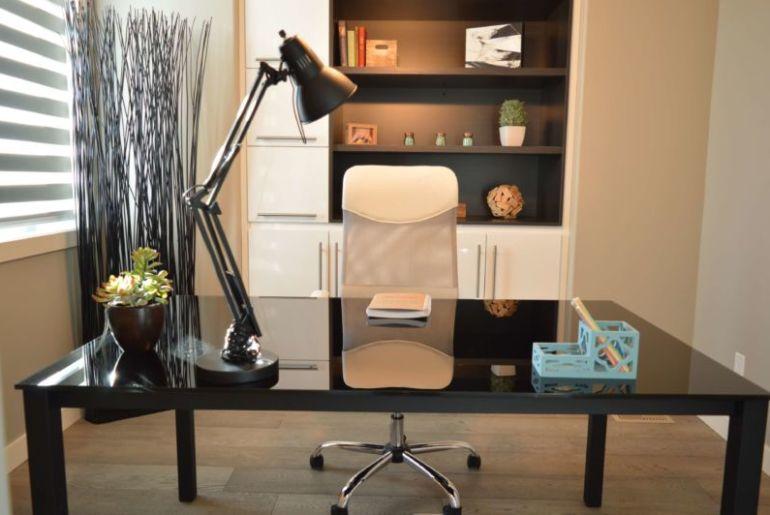 foto de um escritório em casa, com mesa preta, cadeira, acessórios, uma janela ao lado e estante ao fundo. Imagem ilustrativa para texto franquia home office