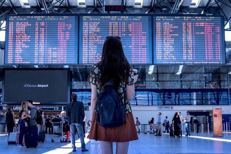 Moça com mochila na frente de um telão de aeroporto. Imagem ilustrativa para texto franquias lucrativas