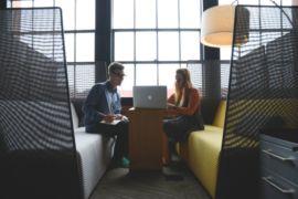 um rapaz e uma moça consultando um computador em um ambiente com dois bancos. Imagem ilustrativa para texto franquia para cidade pequena.