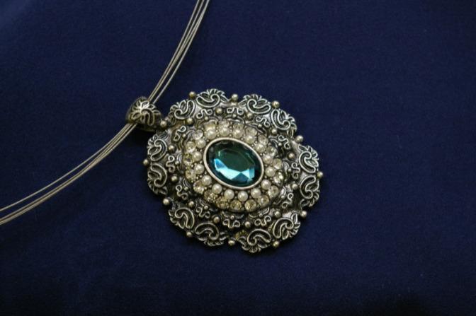 Foto de um colar com pingente redondo com pedra.