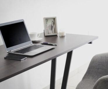 Foto de uma mesa com computador, celular e porta retratado ao lado. Imagem ilustrativa para texto microfranquias.