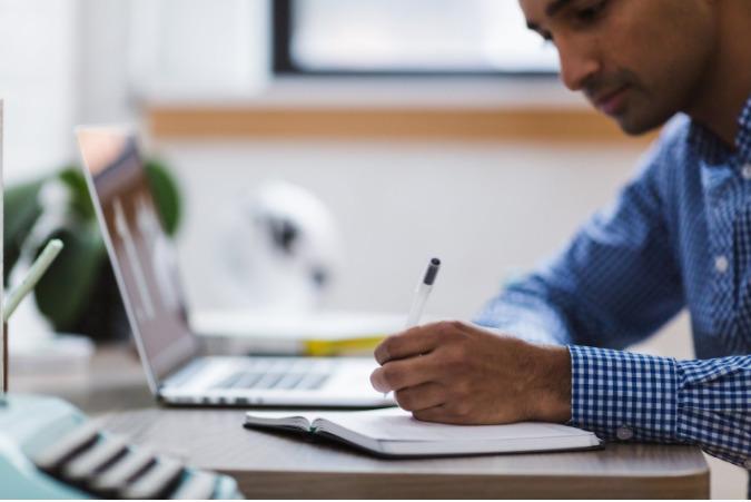 Foto de um homem fazendo anotações em um caderno, com um computador ao lado. Imagem ilustrativa para texto franquia para investir.