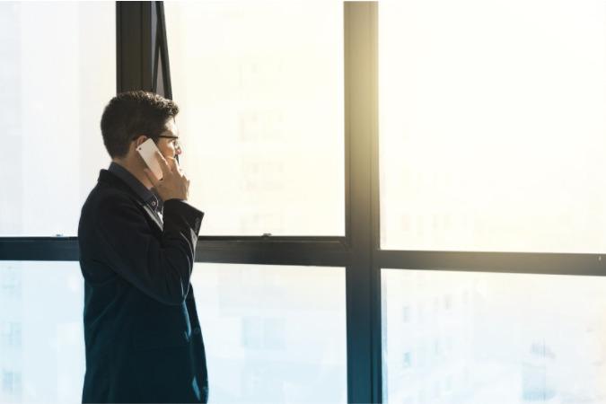 Foto de um homem falando ao telefone ao lado de uma janela. Imagem ilustrativa para texto franquia para investir.