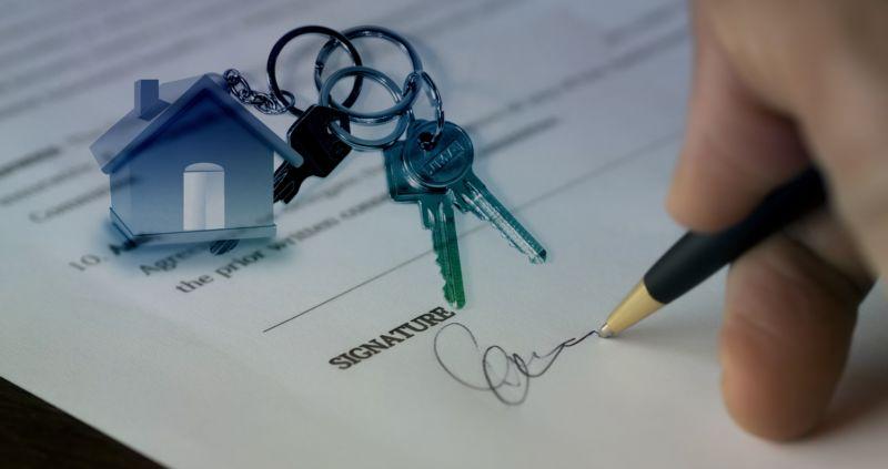 Foto da mão de uma pessoa assinando um contrato com uma chave de casa ao lado. Imagem ilustrativa para texto franquia de seguro.