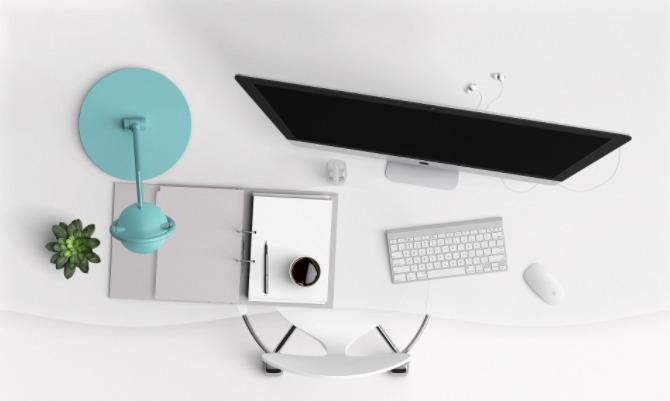 Foto de um computador em mesa branca, com caderno, luminária e planta ao lado.