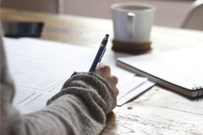 Foto de uma pessoa fazendo anotações em uma mesa cheia de papéis. Imagem ilustrativa para texto trabalhar sozinho.