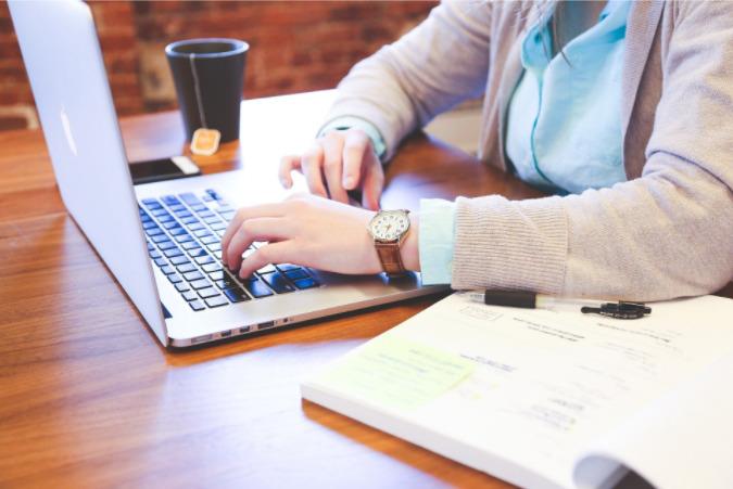 Foto de uma mulher usando computador em uma mesa com livro ao lado.