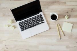 Foto de um computador em uma mesa de madeira com lápis, café e papéis amassados ao redor. Imagem ilustrativa para texto trabalhar sozinho.