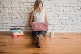 Foto de uma mulher sentada no chão com computador, livros e uma caneca. Imagem ilustrativa para texto melhor negócio para investir.